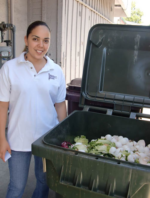 Woman standing next to food recycling bin